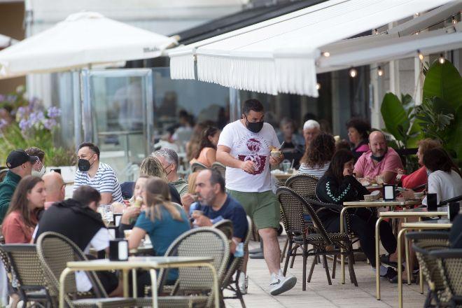 Clientes disfrutan en una terraza en A Mariña, Lugo, Galicia. La hostelería es uno de los sectores que más empleo ha generado en julio.
