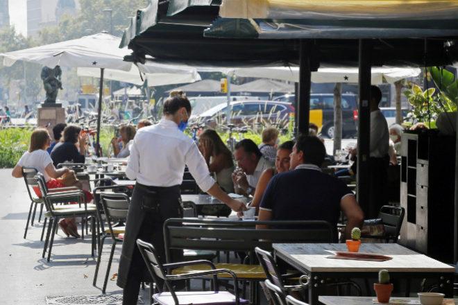 Un camarero atendiendo a clientes en un bar de Barcelona.