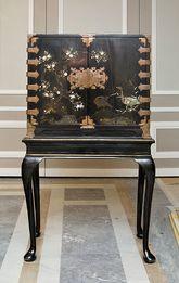 Cómoda realizada en madera lacada en negro con decoración vegetal en...