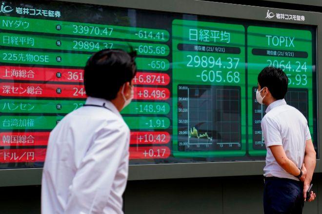 Pantallas bursátiles en Tokio con la cotización de los índices Nikkei y Topix. El Nikkei cedió ayer un 2% por el temor de los inversores a una quiebra de Evergrande.