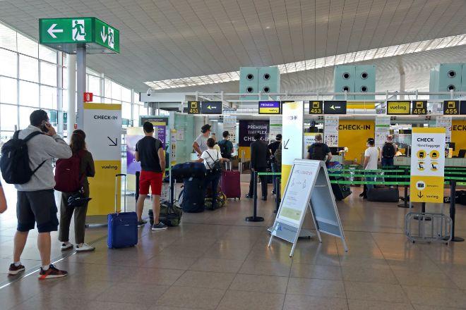 Viajeros esperan a facturar delante de los mostradores de Vueling.