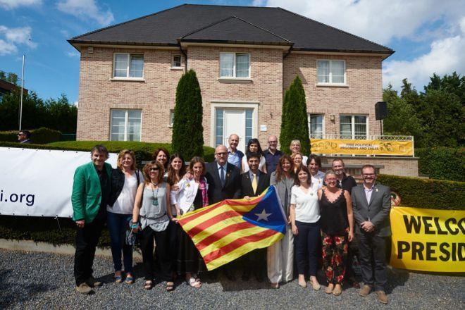 Militantes y dirigentes de Junts junto al expresident de la Generalitat Carles Puigdemont durante una visita a la mansión donde reside en Waterloo (Bélgica).