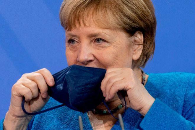 Merkel cubriéndose la boca con una mascarilla tras una reunión con las autoridades sanitarias. JOHN MACDOUGALL / AFP