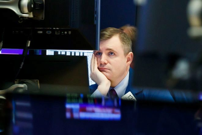 Imagen de un <em>trader</em> entre pantallas con información bursátil