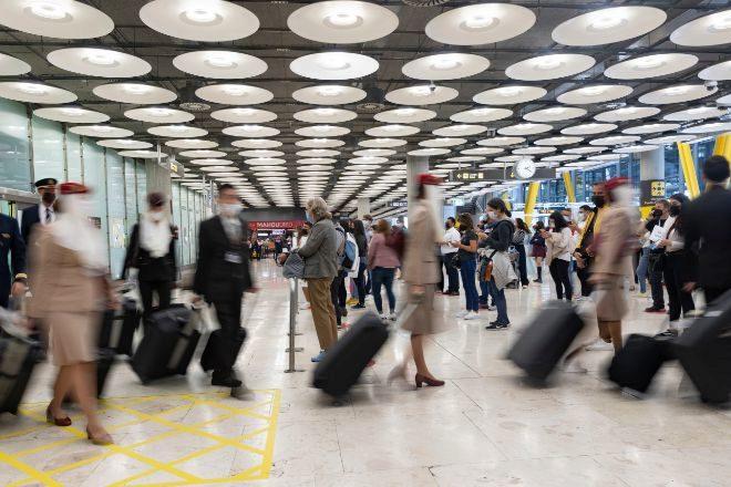 Un hombre espera mientras otros pasajeros llegan a la Terminal T4 del Aeropuerto Adolfo Suárez Madrid - Barajas.