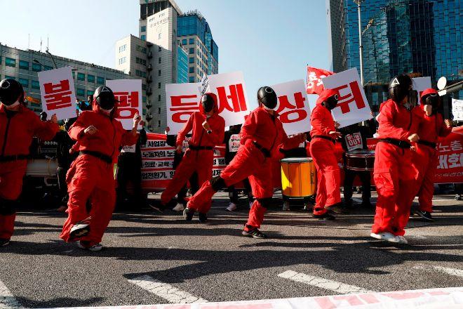 Miembros de la confederación surcoreana de sindicatos llevan disfraces inspirados en el Juego del Calamar.
