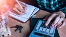 Imagen de un hombre utilizando una calculadora y tomando anotaciones