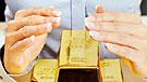 Imagen de manos rodeando lingotes de oro