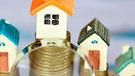 Imagen de una lupa sobre miniaturas de viviendas