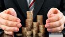 Imagen de un hombre de negocios rodeando monedas con sus manos