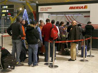 Varios pasajeros hacen cola frente a la oficna de Iberia en la T4 para reclamar sobre sus vuelos canceladios o retrasados, tras más de un mes de huelga encubierta de los pilotos.
