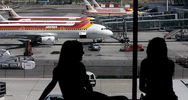 En la imagen de archivo, del 29 de julio de 2008, varios aviones de Iberia permanecen estacionados en la T-4 del aeropuerto de MADRID BARAJAS. EFE/Javier Lizón