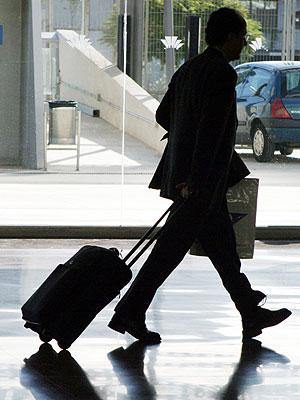 Un hombre de negocios tira de su maleta en el aeropuerto de Barcelona. EXPANSIÓN/Elena Ramón
