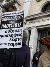 """Un servidor público sostienen una pancarta delante de una oficina del Banco Nacional de Grecia en la que se lee """"los ricos deberían pagar los impuestos"""", durante una manifestación en el centro de Atenas"""