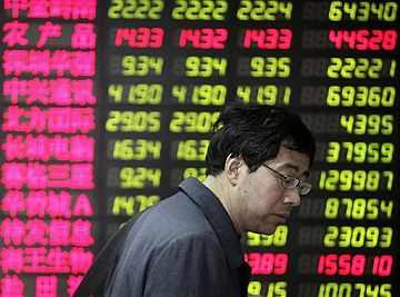 Un inversor junto a las pantallas de la Bolsa de Shangai. Fuente: AP / Eugene Hoshiko