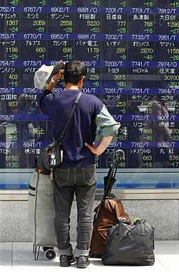Transeunte observando las pantallas electrónicas de la Bolsa de Tokio. Fuente: AP/ Shizuo Kambayashi