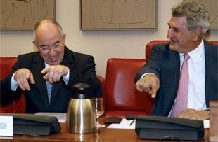 El gobernador del Banco de España (izda.) conversa con el presidente de la Comisión de Presupuestos del Congreso, Jesús Posadas, antes de iniciar su comparecencia ante ese órgano.